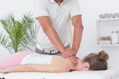 Physiotherapist doing neck massage to his patient Stock Images
