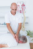 Physiotherapist doing neck massage to his patient Stock Image