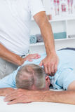 Physiotherapist doing neck massage to his patient Stock Photos