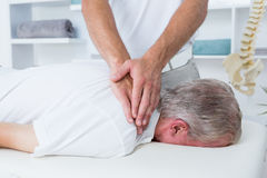 Physiotherapist doing neck massage to his patient Royalty Free Stock Images