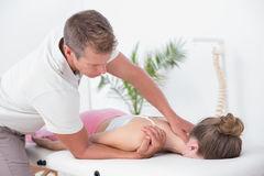 Physiotherapist doing neck massage to his patient Stock Photography