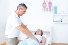 Physiotherapist doing stomach massage to his patient Stock Photography