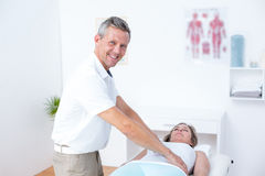 Physiotherapist doing stomach massage to his patient. In medical office Royalty Free Stock Photography