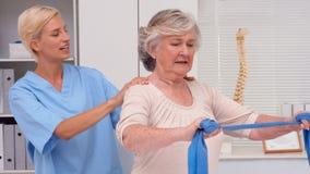 Physiotherapist examining elderly patients back stock video