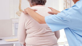 Physiotherapist examining elderly patients back stock footage