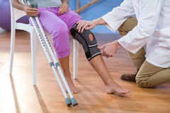 Physiotherapist examining female patients knee Royalty Free Stock Images