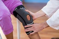 Physiotherapist examining female patients knee Stock Photos