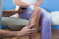 Physiotherapist examining female patients knee with goniometer Stock Photos