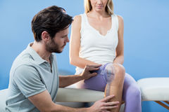 Physiotherapist examining female patients knee with goniometer Royalty Free Stock Photos