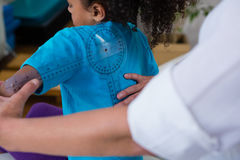 Physiotherapist examining girl patients back with goniometer Royalty Free Stock Photo