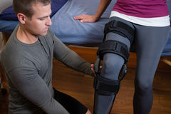 Physiotherapist examining his patients knee. In clinic Royalty Free Stock Photos