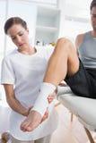 Physiotherapist examining leg of man with bandage Stock Images