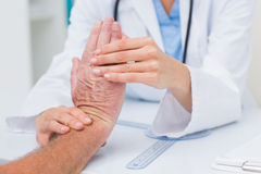 Physiotherapist examining male patients wrist Royalty Free Stock Photography