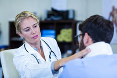 Physiotherapist examining neck of patient. In the clinic stock images