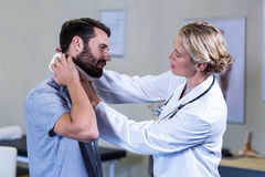 Physiotherapist examining neck of patient. In the clinic royalty free stock image