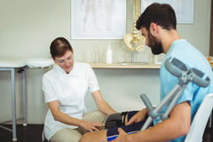 Physiotherapist examining patients knee Royalty Free Stock Images