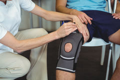Physiotherapist examining patients knee Stock Image
