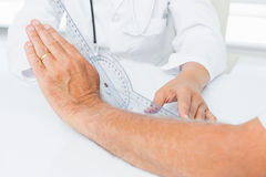Physiotherapist examining patients wrist with goniometer Stock Images