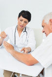 Physiotherapist examining patients wrist with goniometer Royalty Free Stock Photography