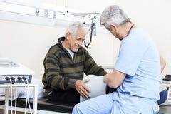 Physiotherapist Examining Senior Patient On Bed. Male physiotherapist examining senior patient on bed at rehab center Royalty Free Stock Photos