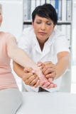 Physiotherapist examining a senior patients hand Stock Photo