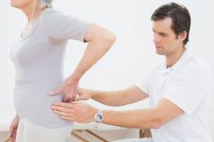 Physiotherapist examining senior womans back Stock Photo