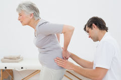 Physiotherapist examining senior womans back Stock Images