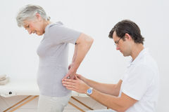 Physiotherapist examining senior womans back Royalty Free Stock Image