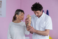 Physiotherapist examining a senior womans wrist. In clinic Royalty Free Stock Image