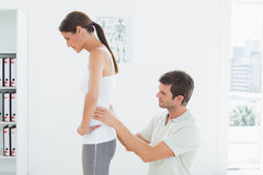 Physiotherapist examining womans back in medical office Royalty Free Stock Image