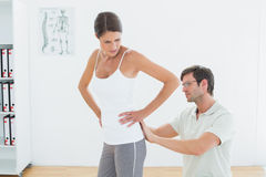 Physiotherapist examining womans back in medical office Stock Image