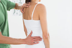 Physiotherapist examining womans back in medical office Royalty Free Stock Photos