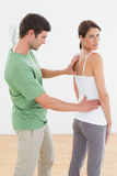 Physiotherapist examining womans back in medical office Stock Images