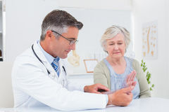 Physiotherapist examining womans wrist with goniometer Stock Photo