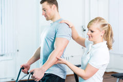 Physiotherapist excercising patient in practice Stock Image