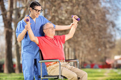 Physiotherapist exercising with a patient in park Royalty Free Stock Photography