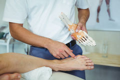 Physiotherapist explaining feet model to patient Stock Photos