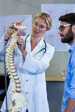 Physiotherapist explaining the spine model to patient Stock Image