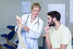Physiotherapist explaining spine model to patient Royalty Free Stock Images