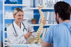 Physiotherapist explaining the spine model to patient Stock Photography