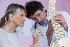 Physiotherapist explaining the spine model to patient Stock Photos