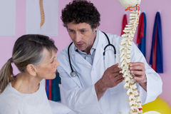 Physiotherapist explaining the spine model to patient Stock Photo
