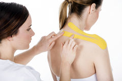 Physiotherapist getting  taping on the trapezius woman. Physiotherapist  puts the taping on the trapezius Royalty Free Stock Photos