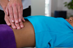 Physiotherapist giving abdomen massage to girl patient Royalty Free Stock Photos