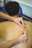 Physiotherapist giving back massage to a patient Royalty Free Stock Image