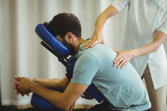 Physiotherapist giving back massage to a patient Stock Photos