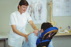 Physiotherapist giving back massage to a patient Royalty Free Stock Images