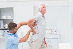 Physiotherapist giving back massage to senior patient Stock Photo
