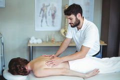 Physiotherapist giving back massage to a woman Royalty Free Stock Photo