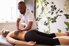 Physiotherapist Giving Female Patient Massage In Hospital Royalty Free Stock Photo